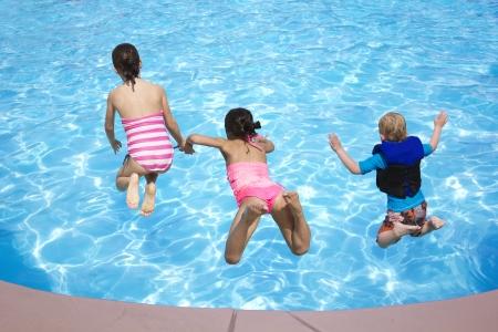 pool fun: Three Kids jumping into the Swimming Pool Stock Photo