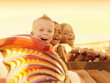 riendo: Ni�os en un Summertime Roller Coaster Ride Foto de archivo