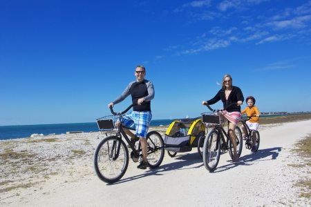 beach cruiser: Family on a beach bicycle ride together Stock Photo