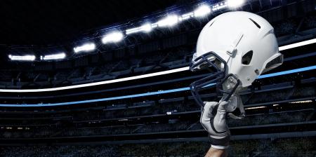 アメリカン フットボール スタジアムで上げられたフットボール用ヘルメット 写真素材