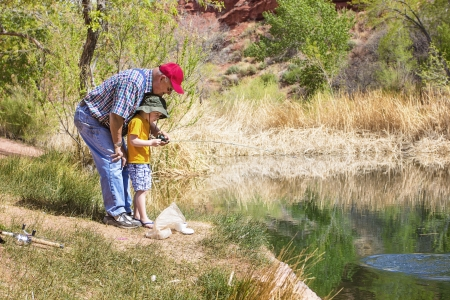 Grandpa fishing with his grandson at a beautiful lake