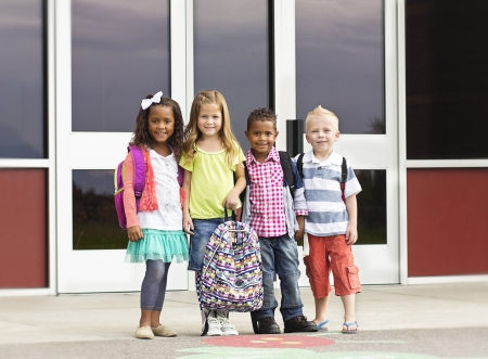 niños saliendo de la escuela: Grupo diverso de niños que van a la escuela Foto de archivo