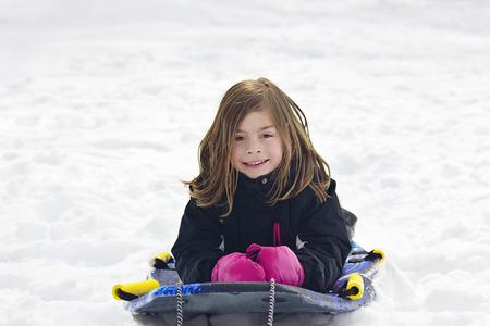 going down: Cute Little Girl going snow sledding down a hill