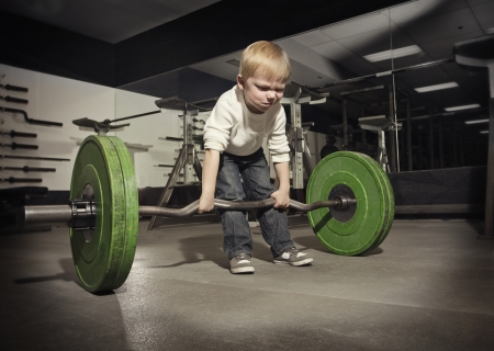 determined: Determined young boy trying to lift a heavy weight bar
