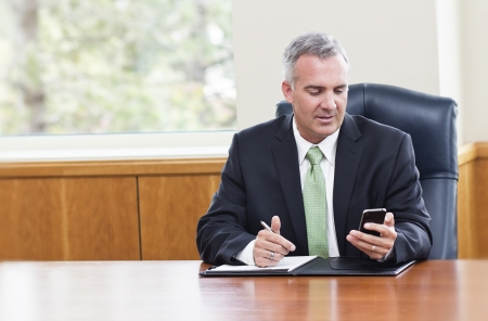 Businessman reading text messages on his phone Stock Photo