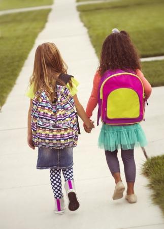 ir al colegio: Ni�as caminando juntos a la escuela, el tono de la vendimia Foto de archivo