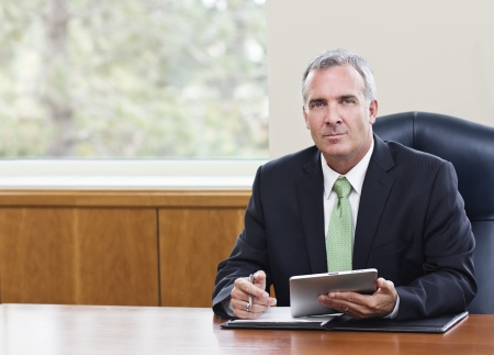 Mature Businessman using tablet computer photo