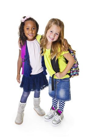 ni�os saliendo de la escuela: Estudiantes lindos escolares joven Diverse aislados en blanco Foto de archivo