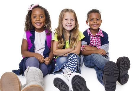 Diverse groep schoolkinderen die op witte Lachend en gelukkige kinderen
