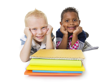 Two diverse little school children with their books Stock Photo