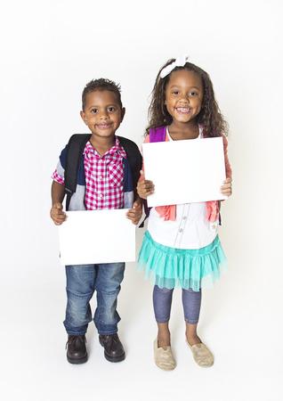 ni�os sosteniendo un cartel: Dos ni�os lindos que sostienen un cartel en blanco