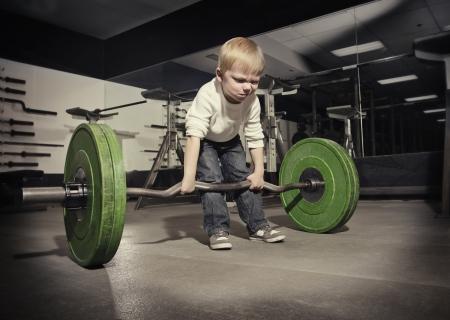 actitud: Niño Determinado tratando de levantar una barra de peso pesado Foto de archivo