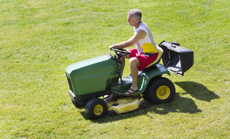 suburbs: Middle-Aged Man Mowing lawn on riding mower Stock Photo