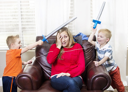 difficult lives: Young Mother overwhelmed by her kids Stock Photo