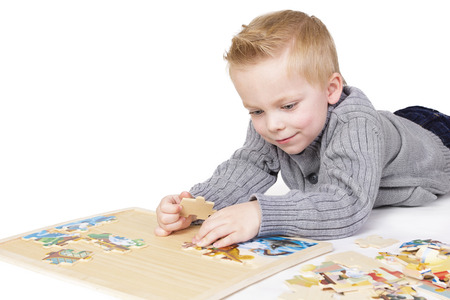 cognitive: Young boy solving a puzzle  Isolated on white Stock Photo