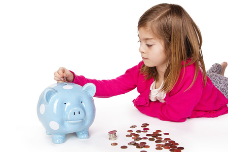Child Saving money in a piggy bank Banco de Imagens