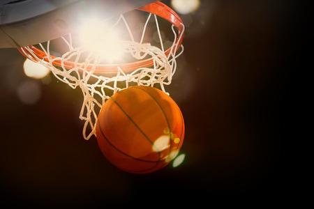 Basketbal gaan door de mand aan een sportarena opzettelijke schijnwerpers Stockfoto
