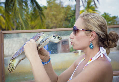 cayman islands: Woman holding and kissing a sea turtle Stock Photo