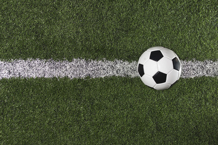 Soccer Ball on the midfield on a Soccer Field Stock Photo