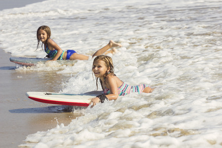 vacationing: Cute little girls boogie boarding in the ocean waves Stock Photo