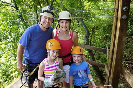 line in: Famiglia godendo di un Adventure Zipline in vacanza Archivio Fotografico