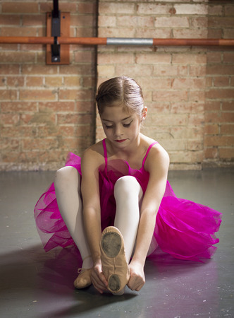 Beautiful young ballerina getting ready for class