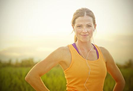太陽フレアを持つ女性のジョガー日没で笑顔