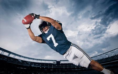 vysoká škola: Hráč amerického fotbalu chytání přistání průsmyku Reklamní fotografie
