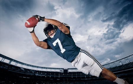 uniforme de futbol: Jugador de fútbol americano La captura de un pase de touchdown Foto de archivo