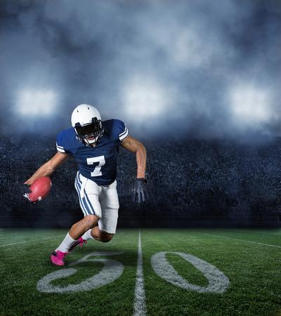 uniforme de futbol: Jugador de f�tbol americano corriendo con el bal�n en un gran estadio