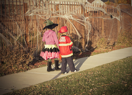 tricks: Halloween kids Trick or Treat in a neighborhood