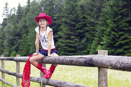 cowgirl boots: Cute young cowgirl portrait on a wooden fence