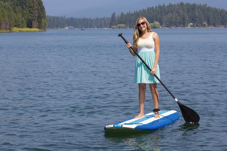 paddleboard: Beautiful woman paddleboarding on scenic lake