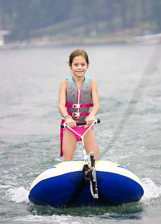 water  skier: Young Girl riding a ski tube behind a boat