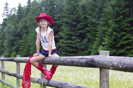 Cute young cowgirl portrait on a wooden fence
