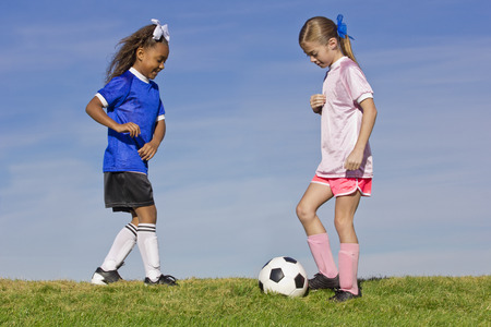 Two young girls playing soccer (simple background)
