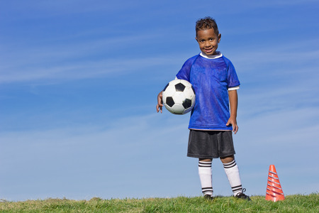 귀여운 젊은 축구 선수가 공을 들고