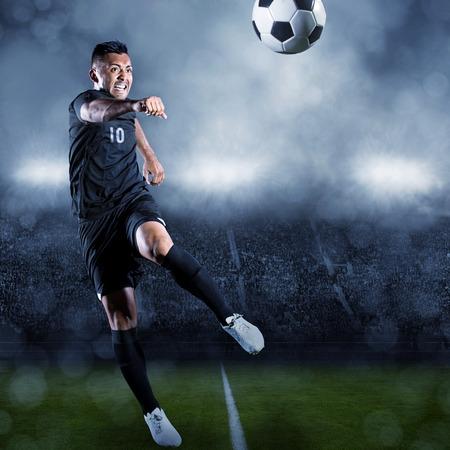 サッカー選手の大規模なスタジアムでボールを蹴る