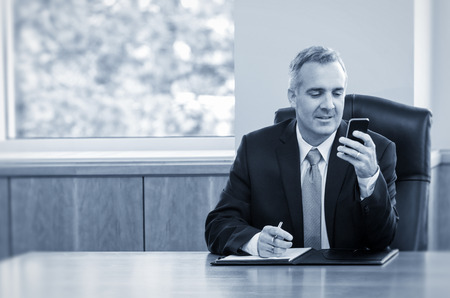 chairman: Businessman reading text messages on his phone Stock Photo