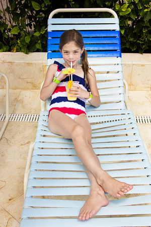 lounge chairs: Child enjoying a tropical drink at an outdoor pool Stock Photo