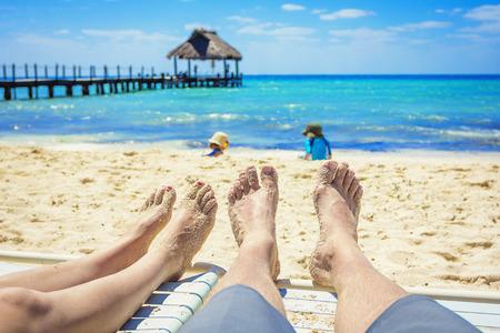 deitado: Pés tan de um casal em cadeiras que apreciam umas férias de praia Imagens