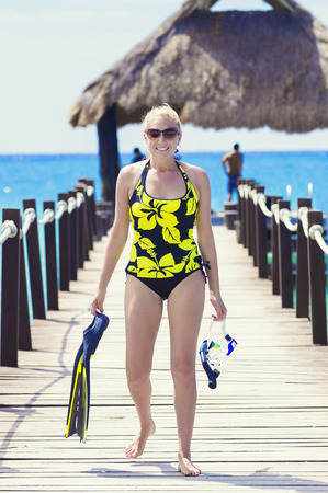 one piece swimsuit: Woman going snorkeling while on a tropical vacation