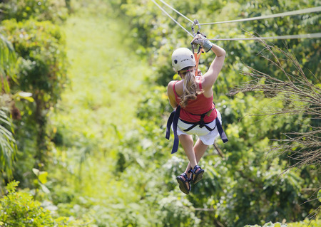 Woman going on a jungle zipline adventure 스톡 콘텐츠