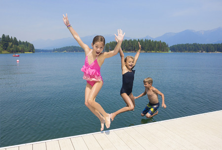 pier: Kids playing at the lake on their summer vacation Stock Photo
