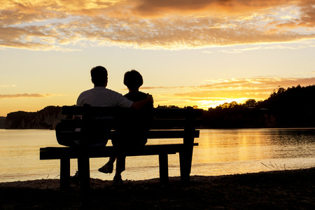 a couple: Couple watching a beautiful sunset together