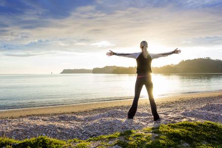 Gezonde gelukkige vrouw genieten van een zonnige ochtend op het strand Stockfoto
