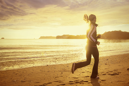early morning: Healthy woman running on the beach at sunset Stock Photo