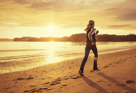 Healthy woman running on the beach at sunset Stock Photo