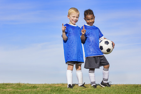 Two diverse young soccer players showing No. 1 sign. Full length view of two youth recreation league soccer players Stock Photo