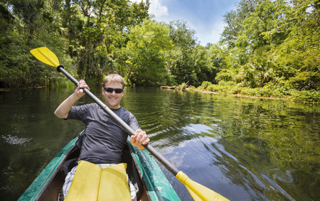 active lifestyle: Smiling, happy man kayaking along a beautiful jungle river. Lots of copy space in an active outdoor lifestyle photo